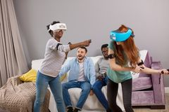 Two multiracial young women dancing wearing virtual reality glasses indoors royalty free stock image