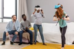 Two multiracial young women dancing wearing virtual reality glasses while their boyfriends sitting on couch and smiling royalty free stock photos