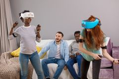 Two multiracial young women dancing wearing virtual reality glasses while their boyfriends sitting on couch and smiling royalty free stock images