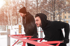Two muscular men doing workout on parallel bars. Winter fitness. Two muscular men doing workout on parallel bars stock photos