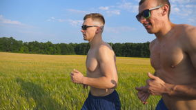 Two muscular men running outdoors. Young athletic guys jogging over the field. Male sportsmans training together at. Nature. Friends exercising outside. Slow Stock Image