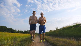 Two muscular men running and talking outdoors. Young athletic guys jogging over the field. Male sportsmans training. Together at nature. Friends exercising stock video