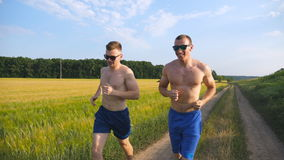 Two muscular men running and talking outdoors. Young athletic guys jogging over the field. Male sportsmans training Stock Images