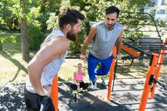 Two muscular young men doing bodyweight exercises in a modern fi. Two muscular young men doing bodyweight exercises for the upper-body motivated by their female Royalty Free Stock Photos