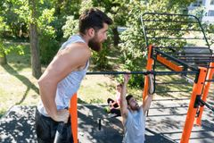 Two muscular young men doing bodyweight exercises in a modern outdoor fitness Stock Image