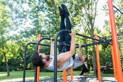 Two muscular young men practicing calisthenics workout in an out. Two muscular young men practicing together calisthenics workout for strength and balance in an royalty free stock photography