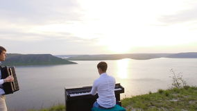 Two musicians Pianist and accordionist playing on the rocks at sunset over sea stock video