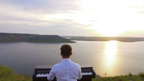 Two musicians pianist and accordionist playing on the rocks at sunset over sea stock video footage