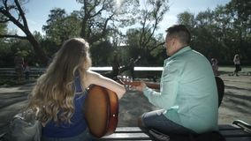 Two musicians play a duet. Guy with a girl playing a guitar in the park stock video