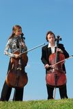 Two musicians play violoncellos against  sky Royalty Free Stock Photos