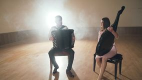 Two musicians playing a black accordion and bandura instrument. Two musicians playing a black accordion and bandura instrument in light room FullHD stock video