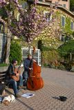 Two musicians playing guitar and contrabass at the Varenna lakefront in a sunny spring day. royalty free stock photography