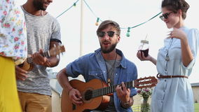 Two musicians playing guitar and ukulele at rooftop, friends dancing. Two handsome musicians playing guitar and ukulele on the rooftop terrace on sunny summer stock footage
