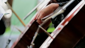 Two Musicians Playing the Violoncello. Close-up. Close-up sideangle shot of the hands of two cellists in action stock video footage