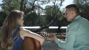 Two musicians are sitting on the bench. Guitarists sit on a bench and play stock footage