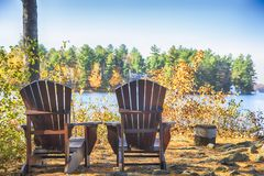 Two Muskoka chairs on a wood dock at a blue lake. Autumn season Stock Photography