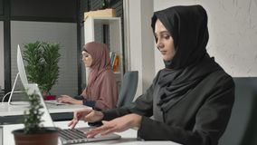 Two Muslim girls in hijabs work in the office, type on the keyboard, look at the monitor and look at the camera at the. End. Focus pull. Office, business, work stock footage