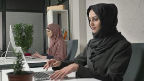 Two Muslim girls in hijabs work in the office, type on the keyboard, look at the monitor and look at the camera at the. End. Office, business, work, women stock footage