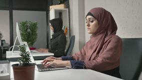 Two Muslim girls in hijabs work in the office, type on the keyboard, look at the monitor and look at the camera at the. End. Office, business, work, women stock video