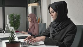 Two Muslim girls in hijabs work in the office, type on the keyboard, look at the monitor. Office, business, work, women. Concept. 60 fps 4k stock video footage
