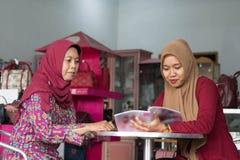 Two Muslim Hijab woman reading a magazine sitting inside their fashion store. Two Muslim Hijab women reading a magazine sitting inside their fashion store royalty free stock image