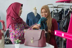 Two Muslim Hijab woman shopping at fashion store. Two Muslim Hijab women shopping a women purse bag, costumer and shop keeper interaction concept - image royalty free stock photography