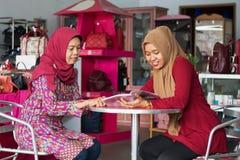 Two Muslim Hijab woman reading a magazine sitting inside their fashion store. Two Muslim Hijab women reading a magazine sitting inside their fashion store stock image