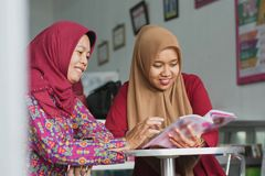 Two Muslim Hijab woman reading a magazine sitting inside their fashion store royalty free stock photos