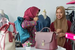 Two Muslim Hijab woman shopping at fashion store. Two Muslim Hijab women shopping a women purse bag, costumer and shop keeper interaction concept - image royalty free stock photos