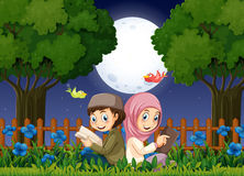 Two muslim kids reading in garden at night Stock Photography