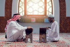 Two muslim men reading Koran in the mosque Stock Photos