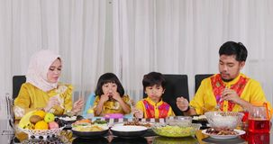 Two muslim parents and children having dinner. Two happy muslim parents and their children having dinner together with various meals on table in dining room at stock video footage