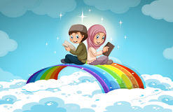 Two muslim reading books over the rainbow Stock Photo
