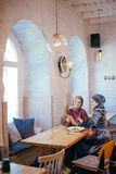 Two Muslim women in cafe, shop online using electronic tablet. Two Muslim women with beauty smile using digital tablet Stock Images