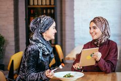 Two Muslim women in cafe, shop online using electronic tablet. Two business partner using tablet in front of their coffee shop Royalty Free Stock Photos