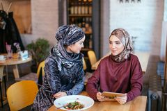Two Muslim women in cafe, shop online using electronic tablet. Two business partner using tablet in front of their coffee shop Royalty Free Stock Photography