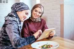 Two Muslim women in cafe, shop online using electronic tablet. Two business partner using tablet in front of their coffee shop Stock Photo