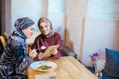 Two Muslim women in cafe, shop online using electronic tablet. Two business partner using tablet in front of their coffee shop Stock Photos