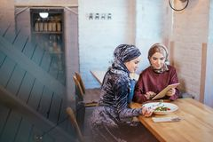 Two Muslim women in cafe, shop online using electronic tablet. Two Muslim women with beauty smile using digital tablet Royalty Free Stock Image