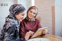 Two Muslim women in cafe, shop online using electronic tablet. Two Muslim women with beauty smile using digital tablet Royalty Free Stock Photos