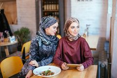 Two Muslim women in cafe, shop online using electronic tablet. Two Muslim women with beauty smile using digital tablet Stock Photo
