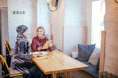 Two Muslim women in cafe, shop online using electronic tablet. Two Muslim women with beauty smile using digital tablet Royalty Free Stock Photo