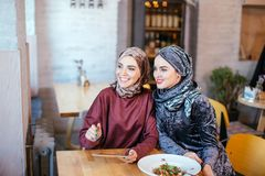 Two Muslim women in cafe, shop online using electronic tablet. Two Muslim women with beauty smile using digital tablet Royalty Free Stock Photography