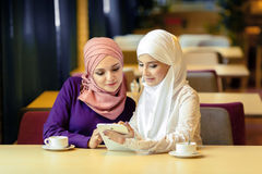 Two Muslim women in a cafe, shop online using electronic tablet Royalty Free Stock Photography