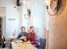 Two Muslim women in cafe, shop online using electronic tablet. Two young Muslim women in cafe, shop online using electronic tablet Stock Photo