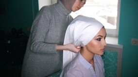 Two muslim women to tie Islamic turban, preparing for a wedding. Two muslim women in front of a mirror to tie Islamic traditional turban, preparing for a wedding stock video footage