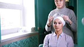 Two muslim women to tie Islamic turban, preparing for a wedding. Two muslim women in front of a mirror to tie Islamic traditional turban, preparing for a wedding stock footage