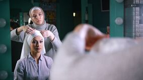 Two muslim women in front of mirror to tie Islamic turban, preparing for a wedding. Preparing for a wedding stock video footage