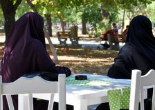 Two Muslim women in a paranjas. Sitting at a table in a cafe in the park Stock Photo