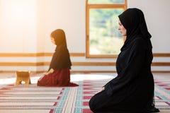 Two Muslim women praying. Inside beutiful mosque Stock Photos